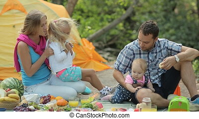 Young parents with two lovely daughters rest in the forest in the fresh air