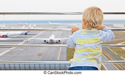 Young passenger looks at the plane in airport - Little baby...