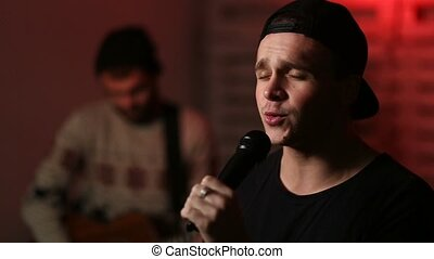 Young passionate male singer performing on stage