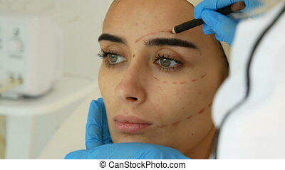 Close-up of plastic surgeon marking woman face before surgery