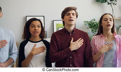 Young patriots standing singing anthem at home before world...