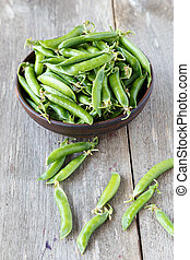 young peas in a clay plate on a wooden table