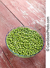 young peas in a clay plate on an old wooden table. Vertical photo