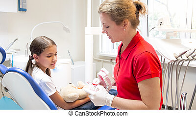 Young pediatric dentist showing teeth model to her patient
