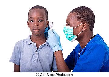young pediatrician doctor examining the ear of a little boy.