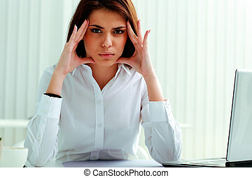 Young pensive businesswoman sitting at the table in office