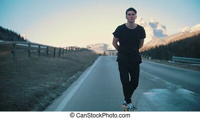 Young pensive man riding on the road with hands under his back balance in a small skateboard in the middle of the Alps