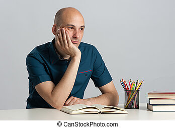 Young pensive man with book