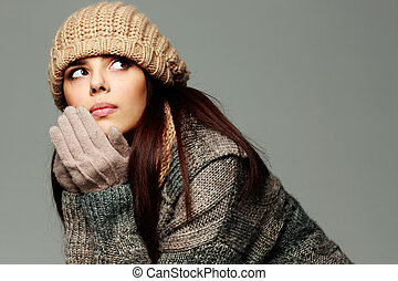 Young pensive woman in warm winter outfit looking away