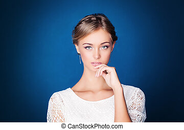 Young Pensive Woman on Blue Background