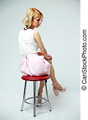 Young pensive woman sitting on the chair over gray background