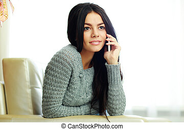 Young pensive woman talking on the phone at home