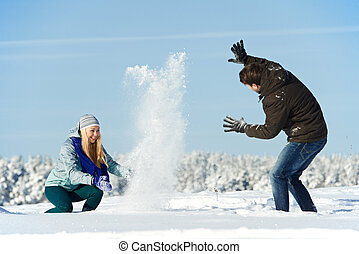 young peolple playing with snow in winter