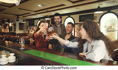 Young people are celebrating something over beer in bar....