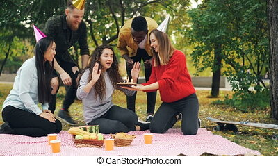Young people are congratulating girl on birthday bringing...