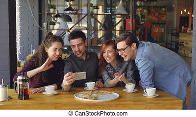 Young people are having video chat holding smartphone looking at webcam chatting to friend at table inside nice cafe. Modern communication and friendship concept.