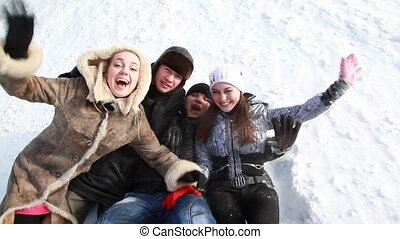 Young people are lying on the snow and laughing.
