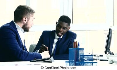 Young people are messy discuss something. One of the businessmen - African American. On the table are located stationery