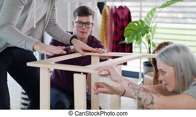 Young people assembling furniture in new home, house sharing...