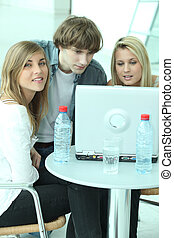 Young people at laptop computer with bottles of water