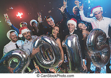 Young people at the New Year party are posing with large shiny inflatable balls in the form of numbers 2019.