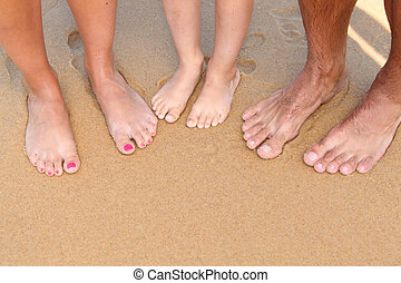 Young people barefoot on the sand