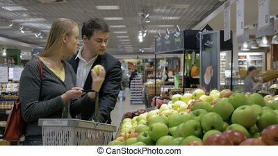 Young people choosing apples in the supermarket