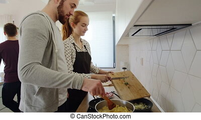 Young people cooking together at home, house sharing concept.