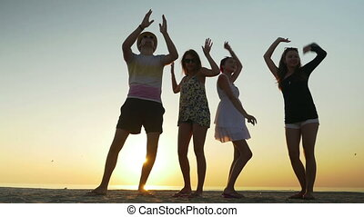 Young people dancing on the beach at twilight