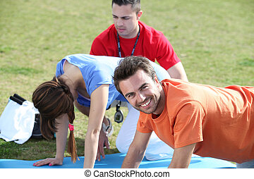 Young people doing press ups in the park