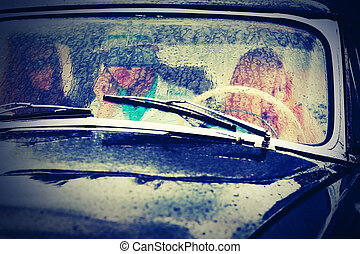 Young people driving vintage car in the rain