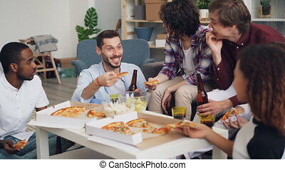 Young people eating pizza chatting and laughing at funny party in apartment