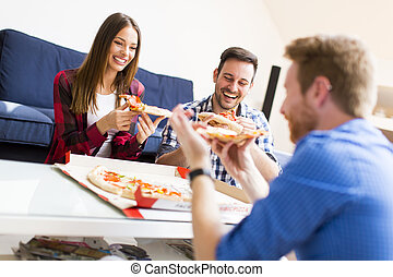 Young people eating pizza in the room
