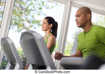 Man and woman working out and running on treadmill in fitness club