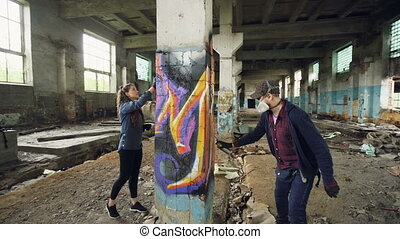 Young people graffiti artists are using aerosol paint to decorate abandoned industrial building with modern graffiti images. Creativity, street art and people concept.