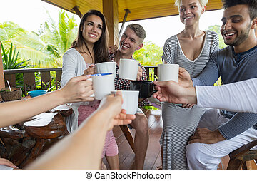 Young People Group Having Breakfast On Terrace Tropical Hotel, Friends Clink Cups Tropic Holiday Vacation