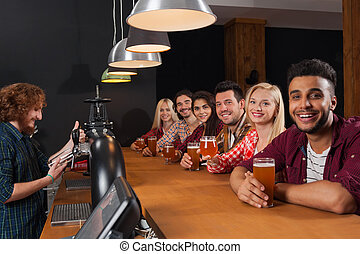 Young People Group In Bar, Barman Friends Sitting At Wooden Counter Pub, Drink Beer