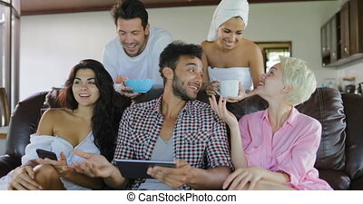 Young People Group Morning Watch TV Sit On Coach In Modern Studio Apartment Talking Use Tablet Computer