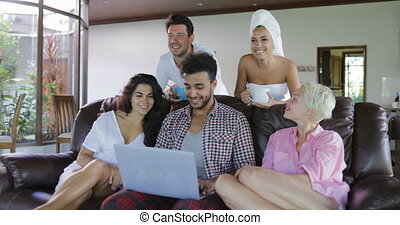 Young People Group Morning Watch TV Sit On Coach In Modern Studio Apartment Talking Use Laptop Computer