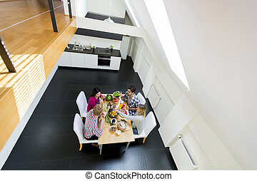 Young people have a dinner in modern kitchen