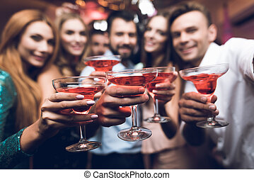 Young people have fun in a nightclub. They drink cocktails and have fun.