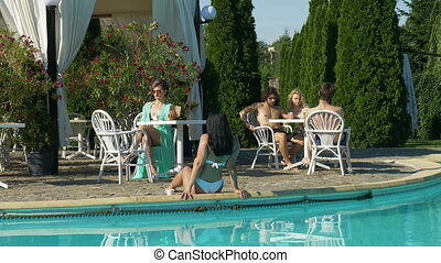 Young people having fun and relaxing by the pool at a villa