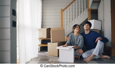 Young people husband and wife are talking and kissing sitting on floor of new house near staircase and dreaming making plans about life in new home. Relocation and youth concept.
