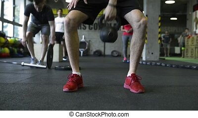 Young people in crossfit gym exercising, man lifting...