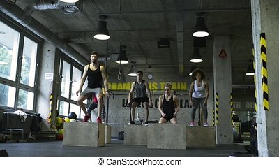 Young people in crossfit gym exercising on wooden boxes. -...