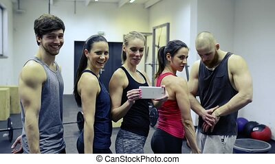 Young people in crossfit gym flexing arms, taking selfie. -...