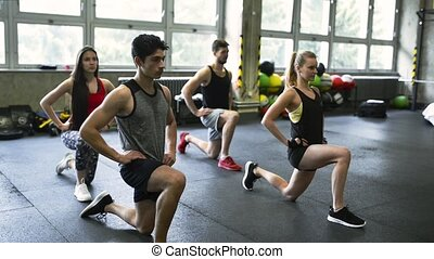 Young people in crossfit gym in lunge position. - Group of...