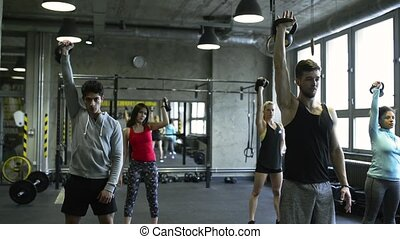 Young people in crossfit gym lifting kettlebells - Group of ...