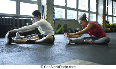 Young people in crossfit gym stretching their legs.