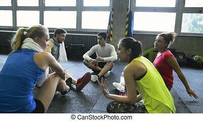 Young people in gym sitting on the floor, talking - Group of...